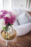 家庭装饰,在咖啡桌上的新鲜的桃红色牡丹在白色roo 免版税库存图片