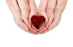 家庭观念-握有心脏的父母的手儿童手 库存图片