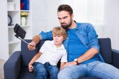 家庭观念-滑稽的年轻采取se的父亲和他的小儿子 免版税图库摄影