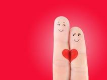 家庭观念-男人和妇女在红色心脏举行 库存图片
