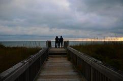 家庭观看日出在海滩 免版税库存照片