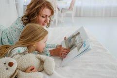 家庭读书上床时间 相当读书的年轻母亲对她的女儿 母亲读一个童话给她的女儿 A 免版税库存照片