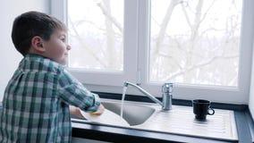 家庭责任,小孩子洗在水槽的盘子在窗口背景  影视素材