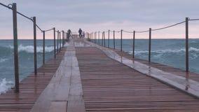 家庭走在风暴的海码头 波浪通过木码头飞溅在海 美好的海景 影视素材