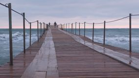 家庭走在风暴的海码头 波浪通过木码头飞溅在海 美好的海景 股票视频
