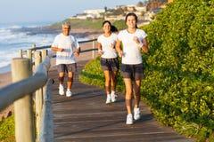 家庭跑步的海滩 免版税库存照片