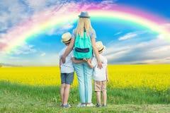 家庭通过花田和神色走在天空的彩虹 免版税库存照片