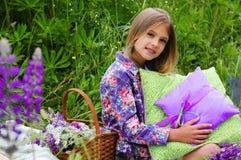 家庭野餐 篮子与花和在有坐垫的一个美丽的小女孩旁边 免版税库存照片