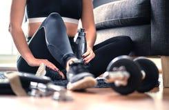 家庭锻炼、重量训练和健身锻炼概念 坐在客厅的运动服的妇女用健身房设备 免版税库存照片