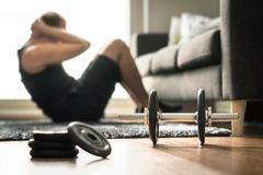 家庭锻炼 在客厅供以人员做ab训练和咬嚼 免版税库存图片