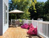 家庭雪松甲板在与开花的庭院的明亮的夏日期间  库存图片