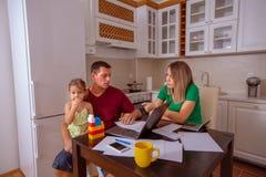 家庭预算和财务男人和妇女有女儿计划的家庭预算的 库存图片