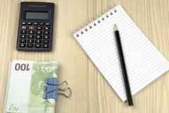 家庭预算 计算器、笔记薄、铅笔和欧元 库存照片