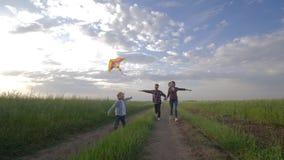 家庭风筝飞行、男孩有年轻母亲的和父亲奔跑在乡下在周末期间在天空背景在自然 股票视频