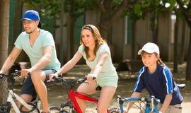 家庭骑马自行车在公园 免版税库存照片