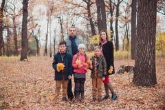 家庭,三个孩子在森林里,停留在秋叶 免版税库存照片