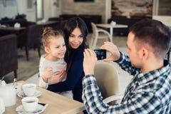 家庭,父母身分,技术,人概念-拍他的小女儿和妻子的照片愉快的父亲由智能手机 库存照片