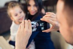家庭,父母身分,技术,人概念-拍他的小女儿和妻子的照片愉快的父亲由智能手机 免版税库存照片