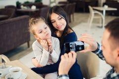 家庭,父母身分,技术,人概念-拍他的小女儿和妻子的照片愉快的父亲由智能手机 库存图片