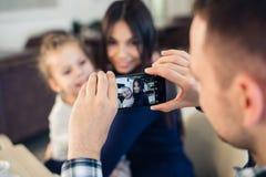 家庭,父母身分,技术,人概念-拍他的小女儿和妻子的照片愉快的父亲由智能手机 免版税库存图片