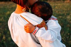 家庭:母亲运载一个男孩 他们在被绣的长袍穿戴 免版税库存照片