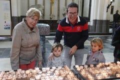 家庭:祖母、父亲和两个女孩姐妹轻的蜡烛在教会里面 免版税库存照片