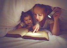 家庭读书上床时间 妈妈和儿童与flashl的阅读书 库存图片