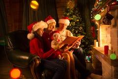 家庭读了故事坐在壁炉前面的沙发在圣诞节装饰的房子内部 免版税图库摄影
