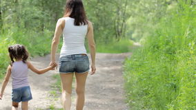 家庭价值观 年轻母亲举行步行的手小孩女孩在公园 backarrow 股票录像