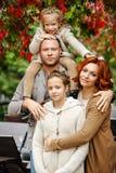 家庭-妈妈、爸爸和两个迷人的姐妹卷曲的同样的 库存图片