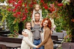 家庭-妈妈、爸爸和两个迷人的姐妹卷曲的同样的 免版税库存照片