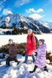家庭(有两个孩子的母亲)在冬天山散步 库存图片