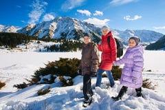 家庭(有两个孩子的母亲)在冬天山散步 免版税库存照片