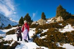 家庭(有两个孩子的母亲)在冬天山散步 图库摄影