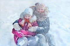 家庭-有她的女儿的母亲-在雪的戏剧,享受愉快的冬天和的感受 免版税库存图片