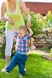 家庭-母亲和孩子在庭院里 图库摄影