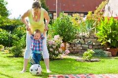 家庭-母亲和孩子在庭院里 免版税库存图片