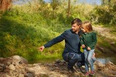 家庭 父亲和女儿由河 库存图片