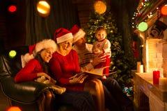 家庭-爸爸、妈妈有女儿的坐沙发和阅读书近由壁炉 库存照片