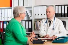 家庭医生审查一个女性前辈 免版税库存图片