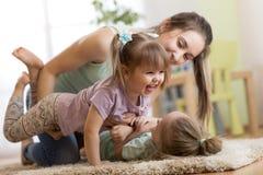 家庭-获得的母亲和的女儿在地板上的一个乐趣在家 一起放松的妇女和的孩子 免版税库存照片