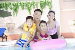家庭画象、母亲、父亲、女儿和儿子,微笑由水池 免版税库存照片