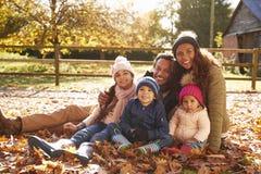 家庭画象在坐在秋叶的步行的 库存照片