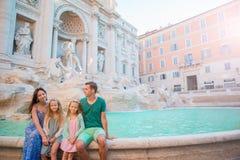 家庭画象在Fontana di Trevi,罗马,意大利 愉快的父母和孩子在欧洲享受意大利假期假日 免版税图库摄影