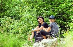 家庭画象坐一座桥梁在森林里 免版税图库摄影