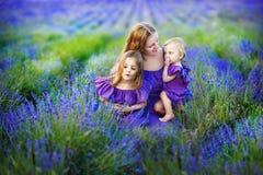 家庭画象-照顾和一个美丽的淡紫色地板的两个女儿 一个强的美丽的家庭的概念 免版税库存图片