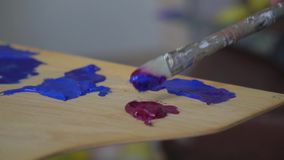 画家慢慢地混合在一个木调色板的一支蓝色画笔 影视素材