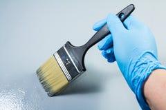 画家手与油漆刷一起使用 免版税库存图片