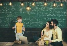 家教 在黑板的家教学生 与父母的家教教育 家庭选择家教 库存照片