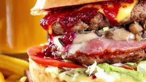 家特写镜头在木桌做了鲜美汉堡用牛肉、蘑菇、烟肉和乳酪 蔓越桔辣调味汁 啤酒 影视素材
